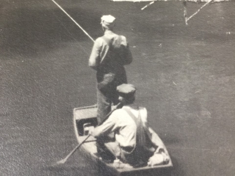 Two men in a rowboat, one sitting down and rowing while the other one is standing and fishing