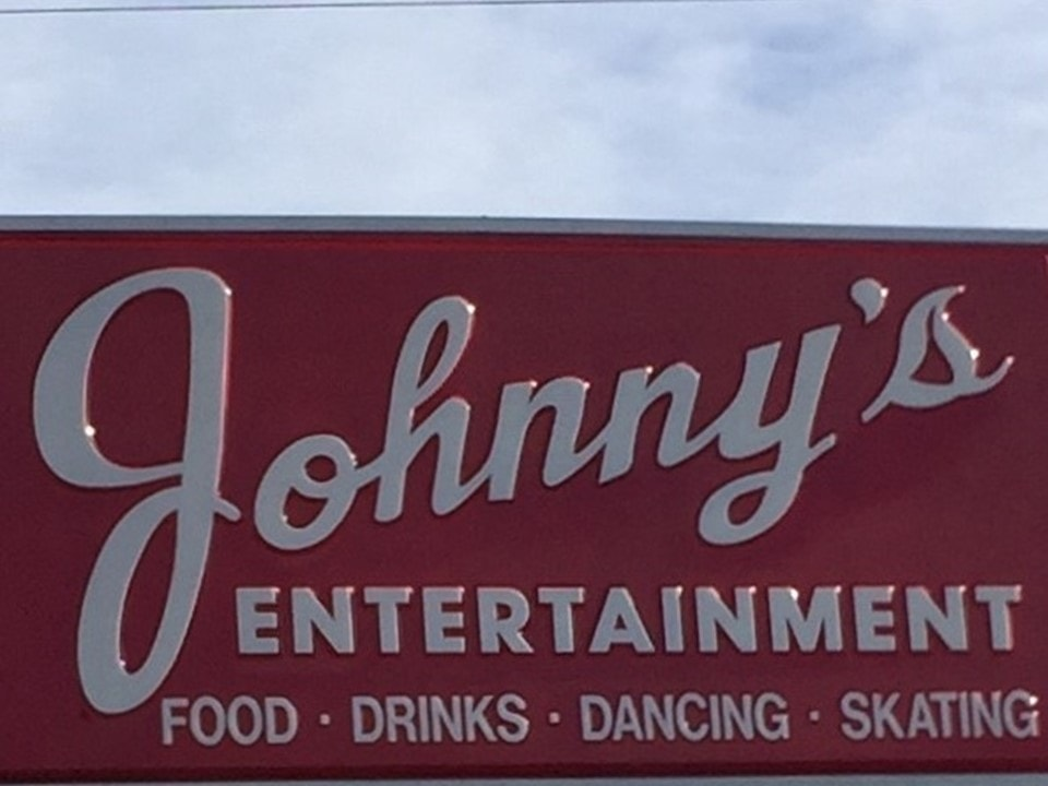 Johnny's Entertainment sign with food, drinks, dancing, and skating