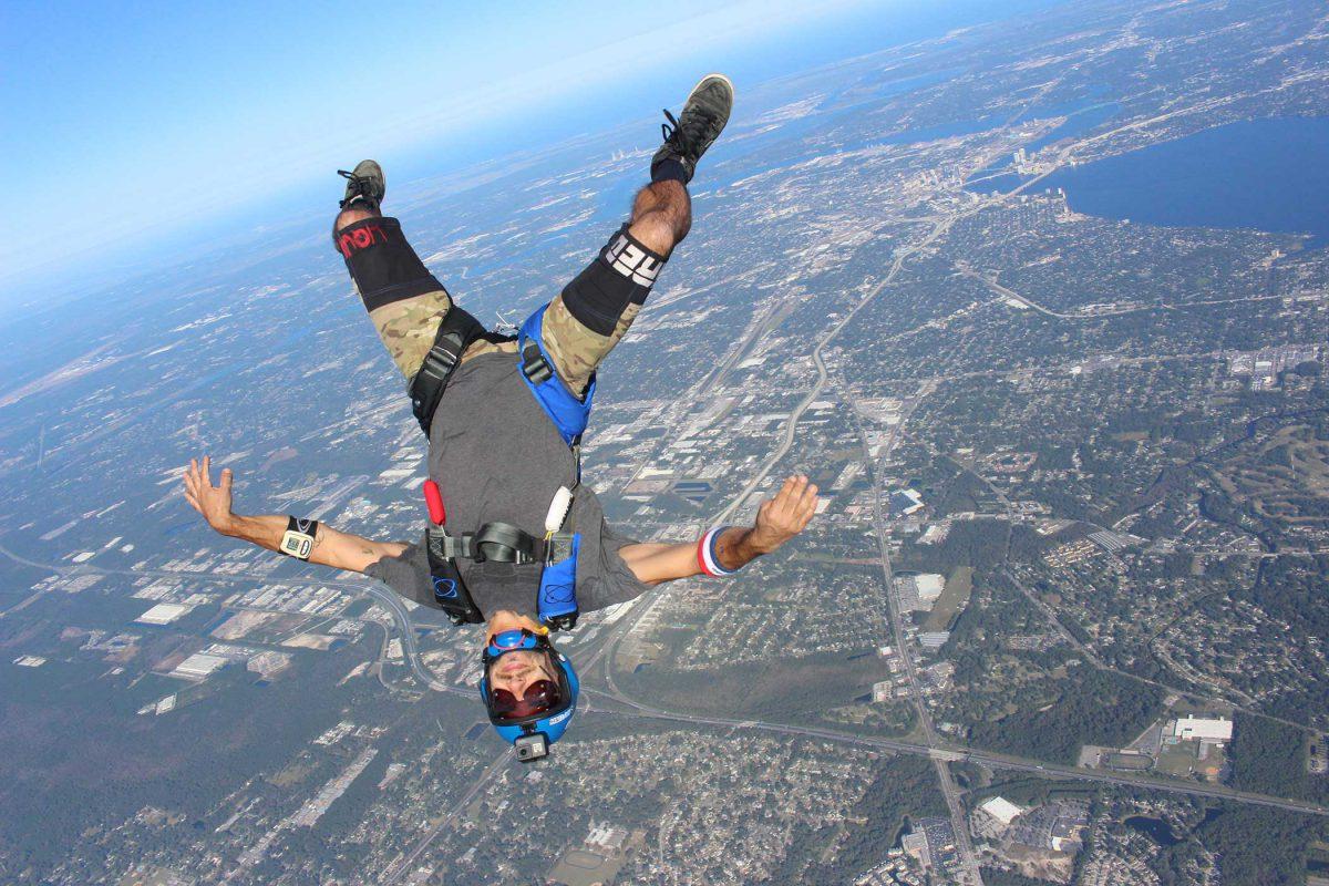 skydiver flies head down in front of St. John's River in Jacksonville FL