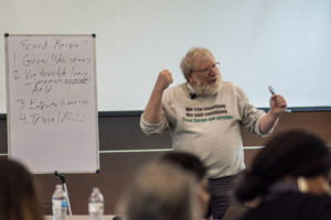 Image: Bill black discussing the recipe for fraud near a white board.