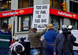 "IMG: Occupy protester holding a ""Too big to fail is too big to allow"" sign outside Bank of America."