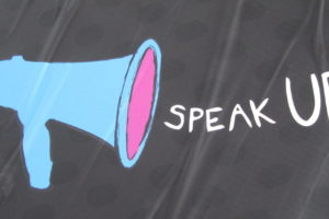 Image of a dark sheet with a blue megaphone and the words Speak Up drawn on it.