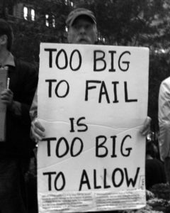 """Black and white image of man holding a sign that says, """"Too big to fail is too big to allow"""" in all capital letters."""