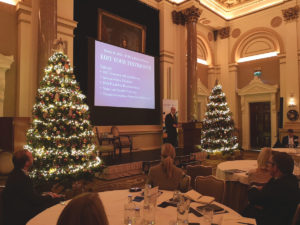 Picture of Richard M. Bowen speaking at IoB conference with Christmas trees on both sides of the projected slides.