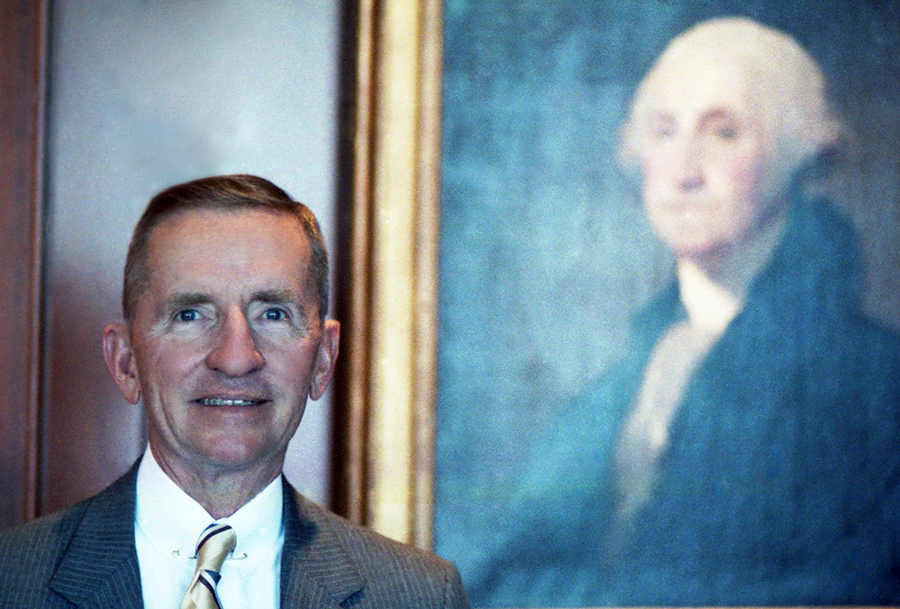 Color portrait of Ross Perot, 1986, standing in front of a portrait of George Washington