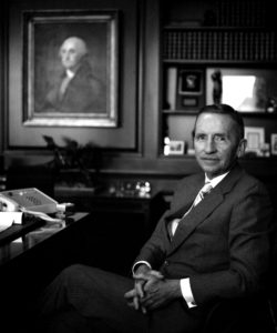 Image: 1986, Ross Perot sits behind his desk, hands folded in his lap, with bookshelves and a portrait of George Washington in the background.