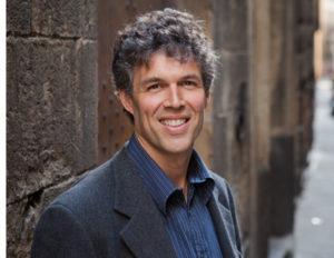 Image of Tom Mueller in gray suite standing against large bricks.