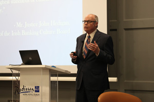 Picture of Richard Bowen presenting near a podium with a projected slide over his right shoulder.