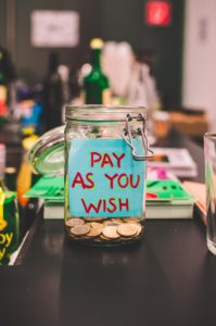 """Image: Open mason jar with coins and """"Pay as you wish"""" note inside"""