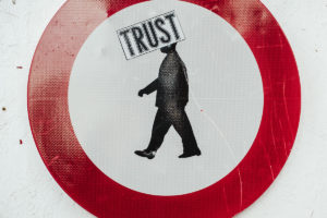 Image of a man walking to the left inside a circle, the word TRUST in a box across his head.