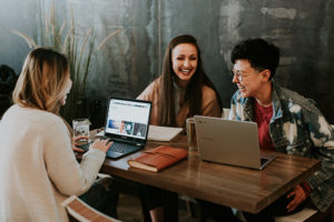 Women laughing and working on laptops together