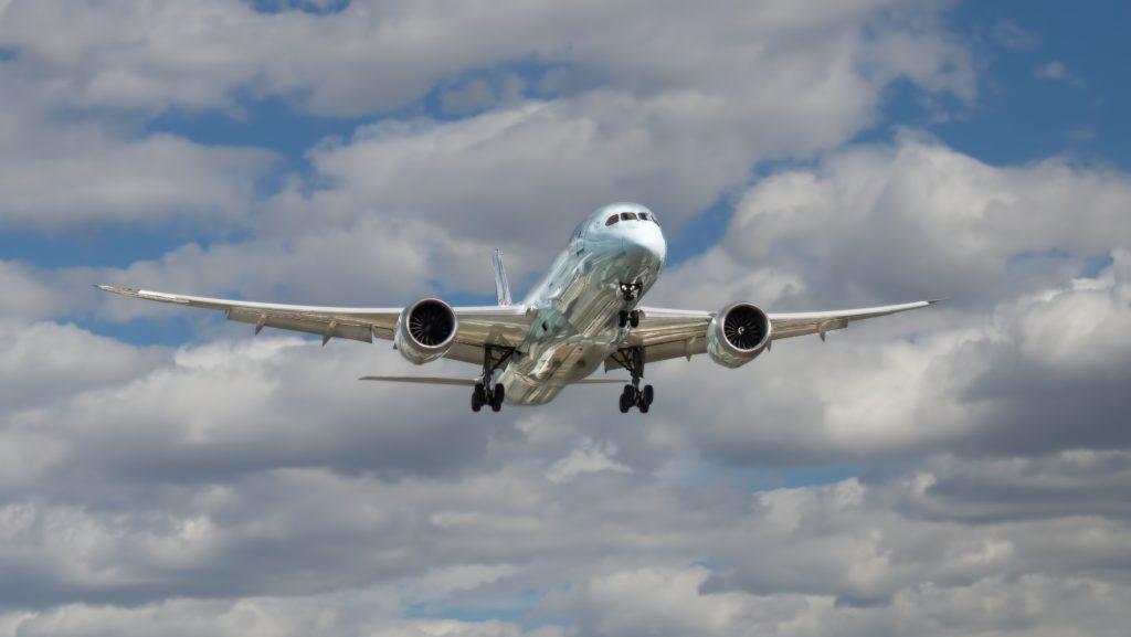 Image: Plane taking off under cumulus clouds