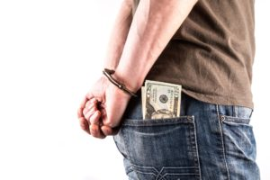 Image: US currency in back pocket of handcuffed person.