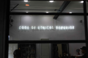 """Image: neon storefront sign that reads: Code of ethical behavior"""""""