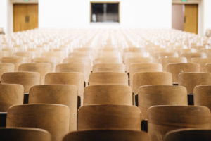 Image of empty wooden seats in a theater or classroom