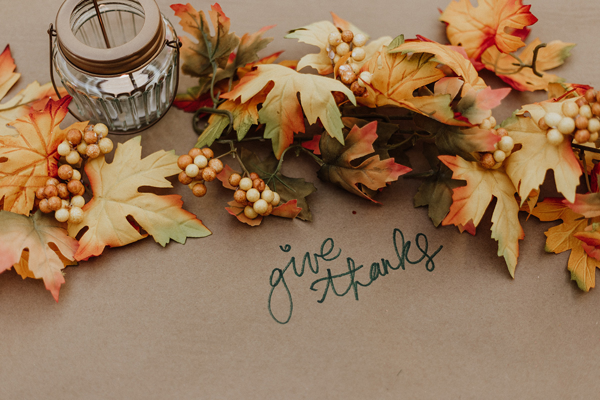 """Fall leaves around a candle wiht """"give thanks"""" written on the table"""
