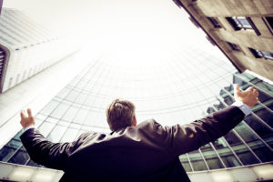 Low angle image of a man with his arms outstretched looking up at a tall glass buildling.