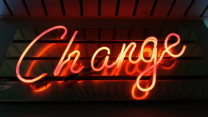"""Image of a neon sign that says """"Change"""" in a cursive font."""