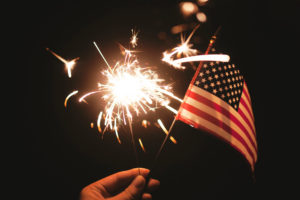 Image: hand holding sparkler and American flag with dark sky behind