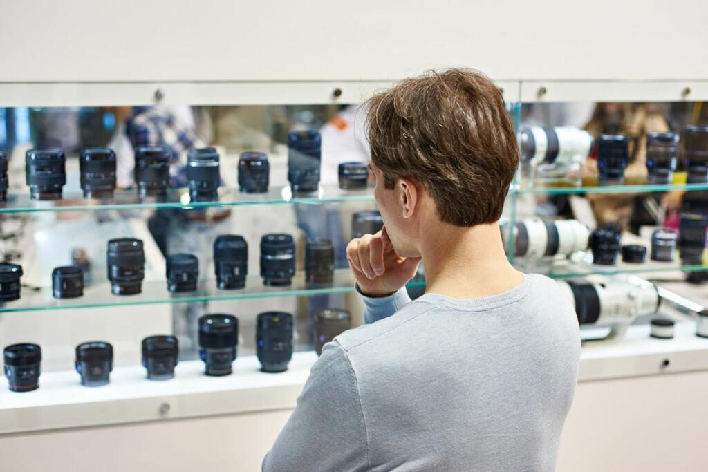 consumer researching and comparing camera lens' brands