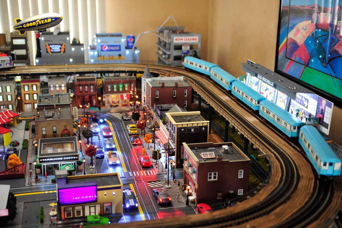 deadhead railways - model trains - blue train elevated over modern city