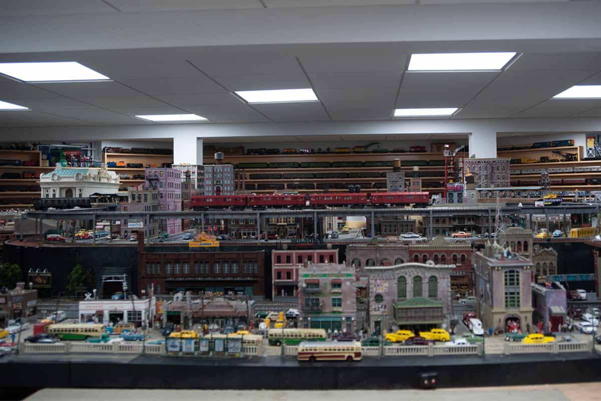 deadhead railways - 2 rail o scale locomotives - red elevated train above city