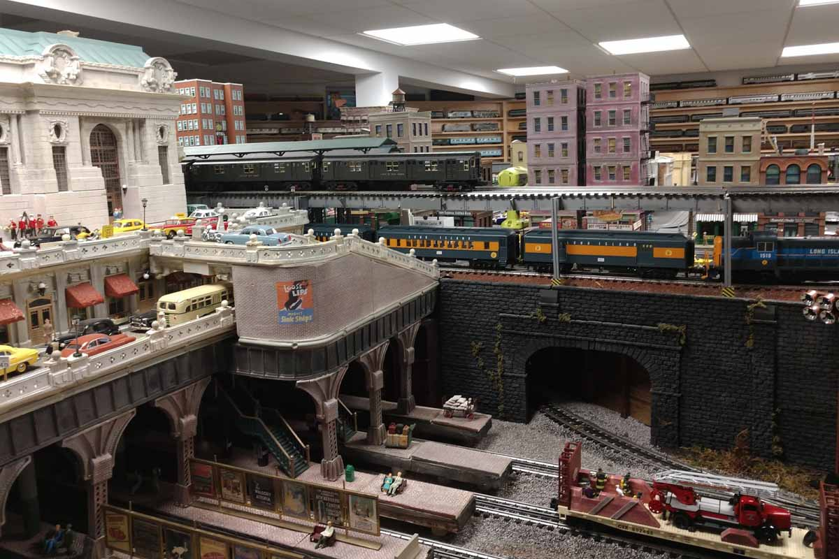 deadhead railways - 0 gauge trains - view of city with a bunch of building in background