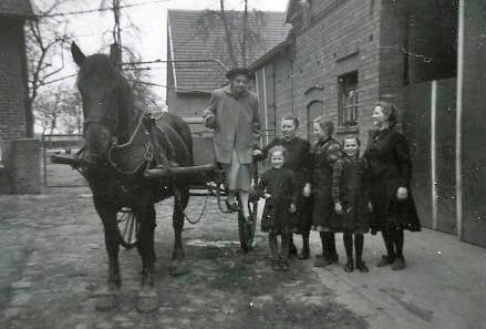 Young girls and an old lady near a carriage