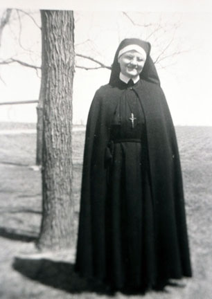 A full image of a smiling nun