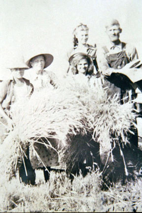 A group of people holding bundles of hay