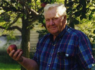 An old man holding an apple