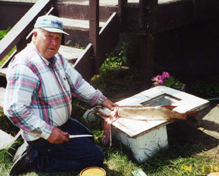 An old man cleaning a fish for a meal