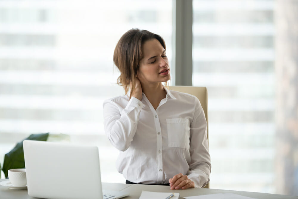 Woman sitting at a desk with neck pain