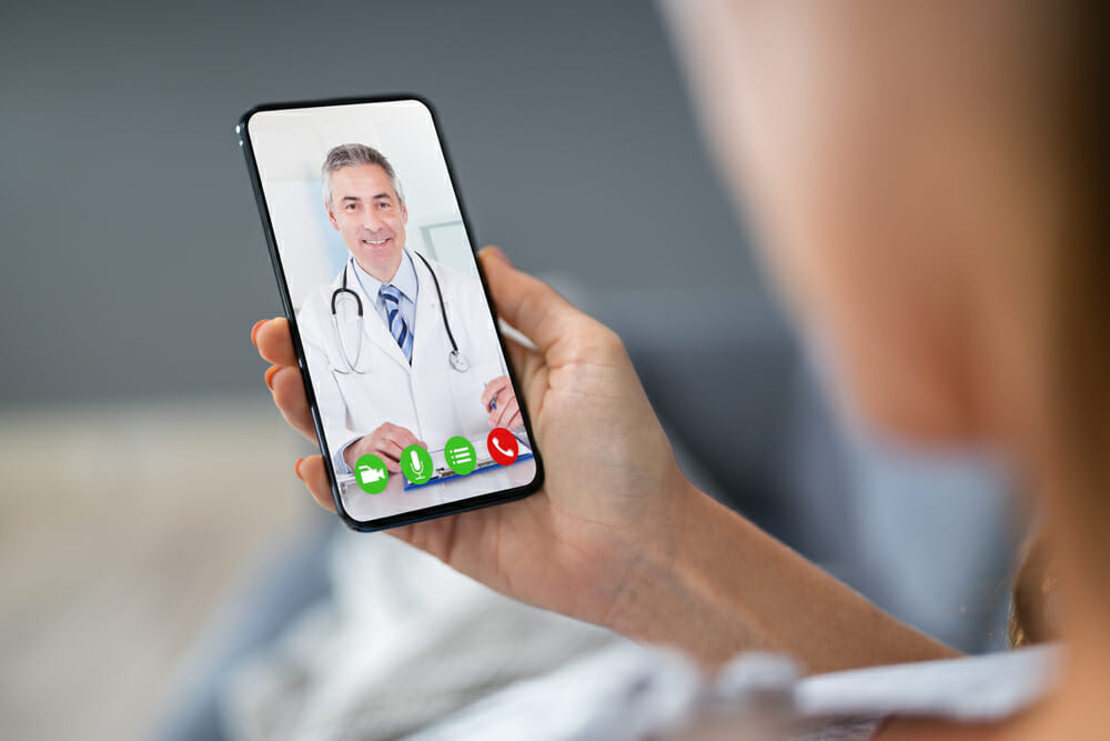 person having telemedicine visit her a doctor on a mobile phone