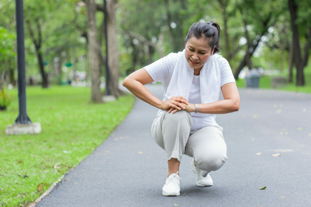 woman in a park holding her knee in pain