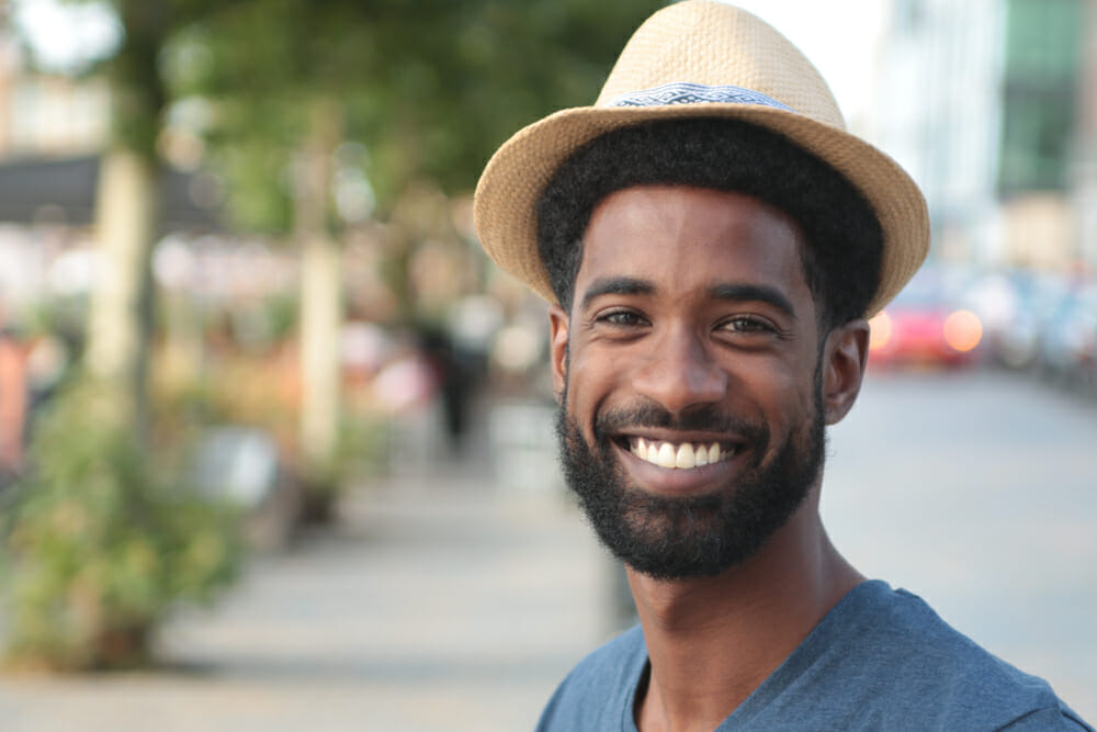 man with a beard smiling in a park