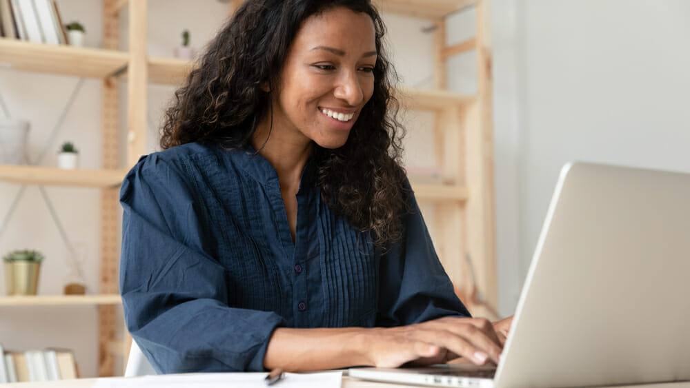 woman smiling while typing on a laptop