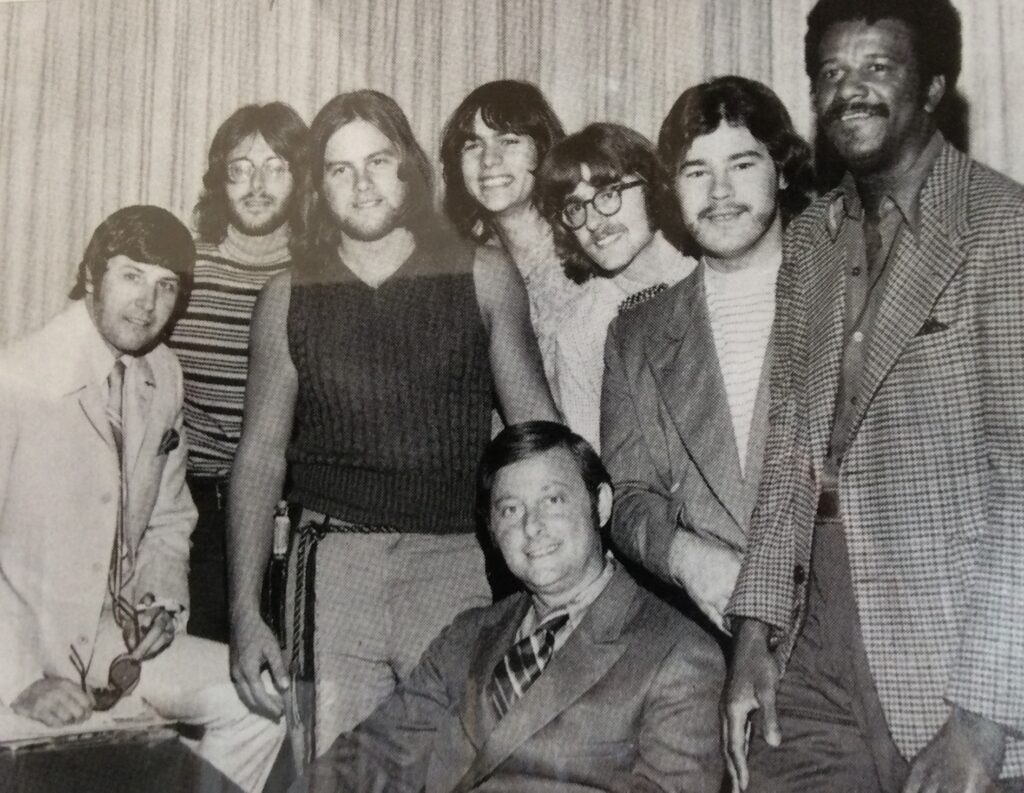 People! with band manager and Wally Amos (right), founder of Famous Amos chocolate chip cookies.