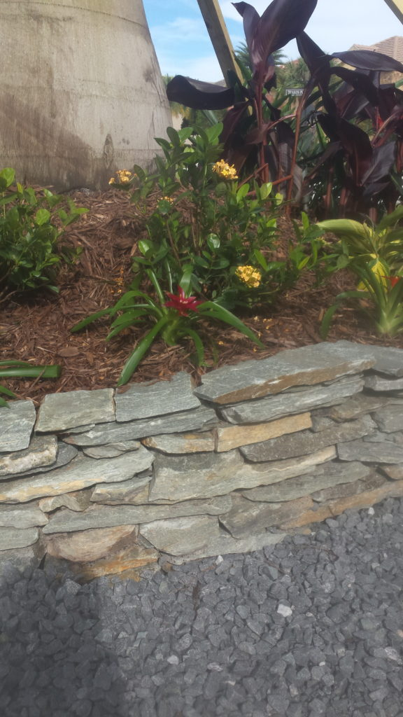 decorative stacked border wall for landscape bed. Stones are set with a firm set bond to hold in place.