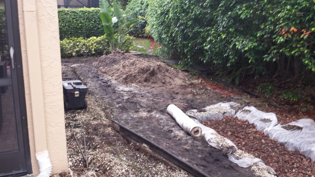 This photo shows the beginning prep work in dealing with the damp drainage problem before the new landscape and rockscape garden in this Boynton beach project was installed. The lawn in the back had to be removed and re-graded by hand to help the water direct towards the back property swale instead of standing in place. To deal with the drainage issue, re-grading of the soil level was done, connections with underground drainage piping were made off of the home's gutter downspouts and run into in ground exit point drains by the back swale. In addition, in this photo, a French drain was added to the most troublesome areas to help collect surface water as well. A good portion of the soil excavated from the French drain worked into the design of elevating the bed areas as seen in the finished photos.