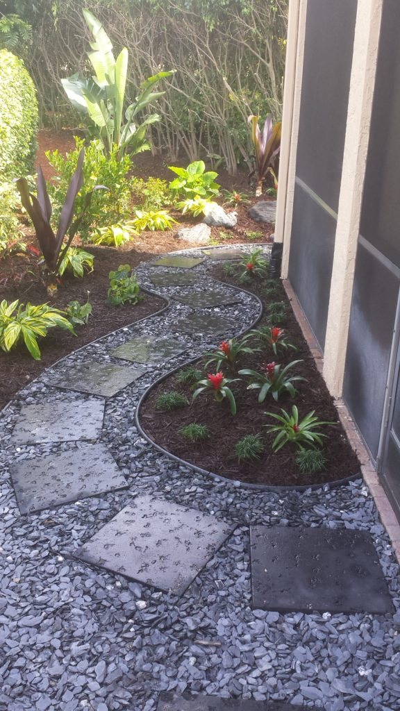 Black Concrete step stones with Black Slate stone (black, grey stones) fill this pathway that is bordered with rubber edging. Wanted to create a relaxed, clean look for a walk through the backyard of this small garden landscape.