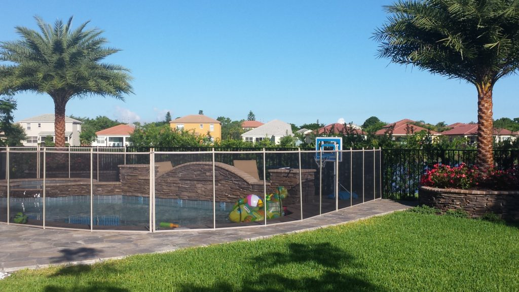 This photo shows a newly completed pool construction with the landscape including elevated planting beds that add a significant part of the overall pool design.  Not part of the original plan, the 2 side elevated beds, which each have a Sylvester palm planted inside them, help to frame out the area and provide a richer look for this small area directly behind and to the sides of the pool.   Stone work, flagstone facing with brick coping adorns the 2 planter walls to help tie in the hardscape with the new swimming pool.