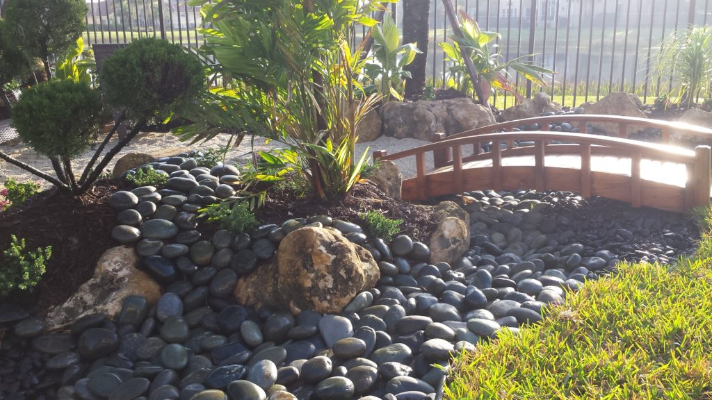 This photo is a close up of a tropical, Asian styled garden using different ground stones for accent and a bridge as a main element in the design.  The Cap Rock Boulders are the larger stones used for soil retention in the garden, with Mexican Beach Pebble and a Black Polished stone represent the stream.  The darker Mexican Beach Pebble & the Black Polished Indonesian stone in the photo represent water in this design.  Universal Landscape, Inc.