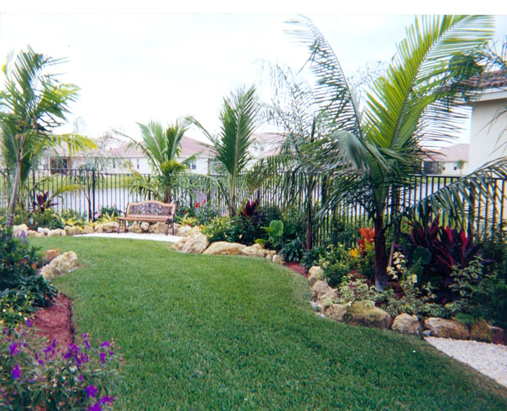 This photo shows the use of natural Florida Cap Rock boulders used to help provide both an accent of interest to the project & a decorative border in places of the landscape bed edging.  The use of rock increases the tropical feel of this design.  Hope you like !  Universal Landscape, Inc.