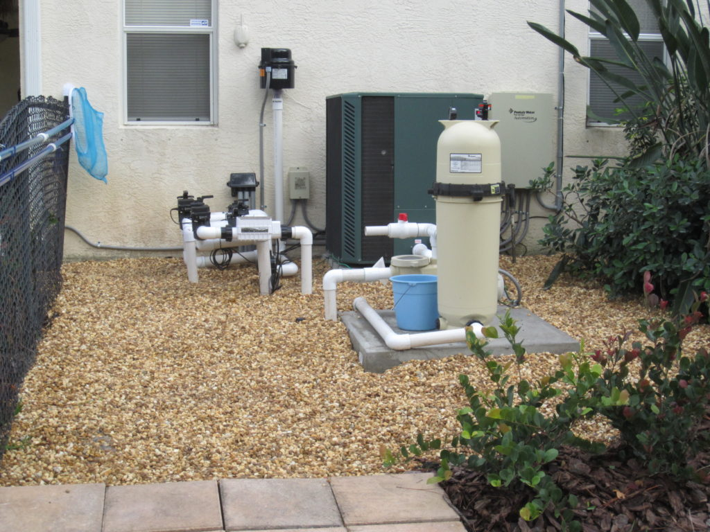 This is an example of a clean area for a pool pump & water purifying system work area.  The rock is less maintenance than a lawn by far, and even mulch, as it needs less re-freshing.  Stone costs more to install because of the labor and cost of material, but, it lasts much longer than mulch for those who are considering which to possibly install.  Universal Landscape, Inc.