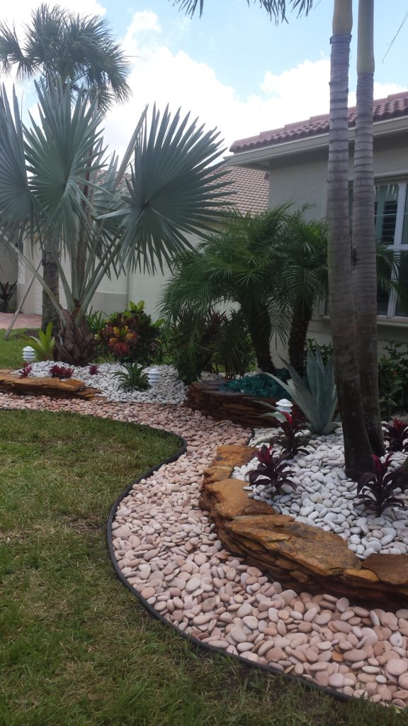 This Delray Beach home wanted a clean look with a good bit of curb appeal 'pop'.  We installed elevated landscape beds accented with Georgia Sunset flagstone, Peach salmon stone serves as an accent in front of the wall.  The white Polar stone sits behind the wall with a Jade colored Glass inset below the center elevated Flagstone wall that seperates and lifts the Robellini palm by center wall window in front of the home.  Red Ti plants along with other tropical accents help to add more interest and contrast to the front view. Hope you like !