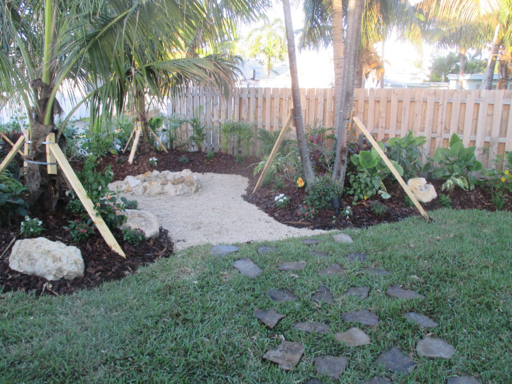 This backyard hangout spot in east Delray Beach is positioned with a view of the canal and across the backyard pool area.  Made to feel like a cozy corner with elevated soil burms, shade with Solitaire & Coconut palms, set in a tropical landscape. That 'beach feel' brought home a little more with crushed shell on the ground, with a Fire pit built from Cap Rock boulders . All the while flagstones set into the lawn help to invite to the area. Hope you like !