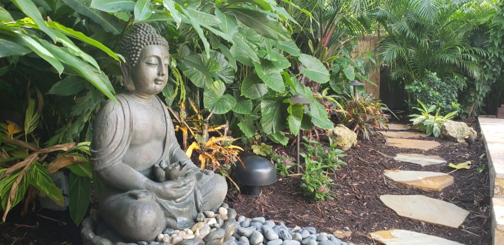 Buddha statuary in garden by walk path, west palm beach