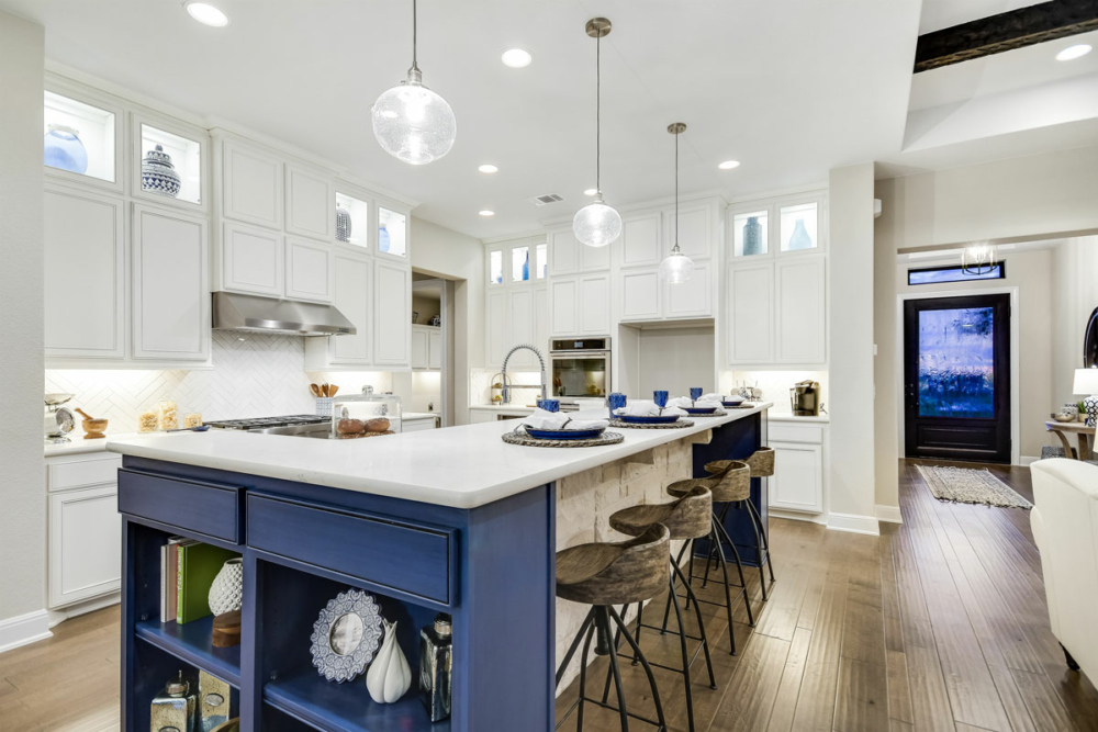 Blue kitchen island cabinets with white perimeter