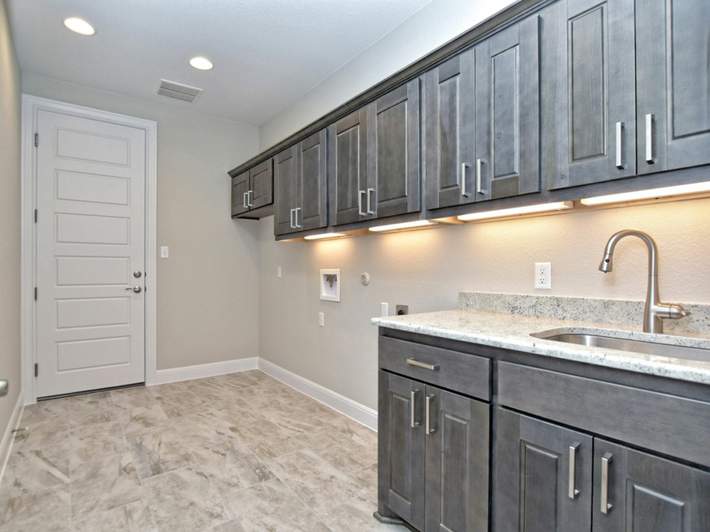 Laundry room with stained wood cabinets